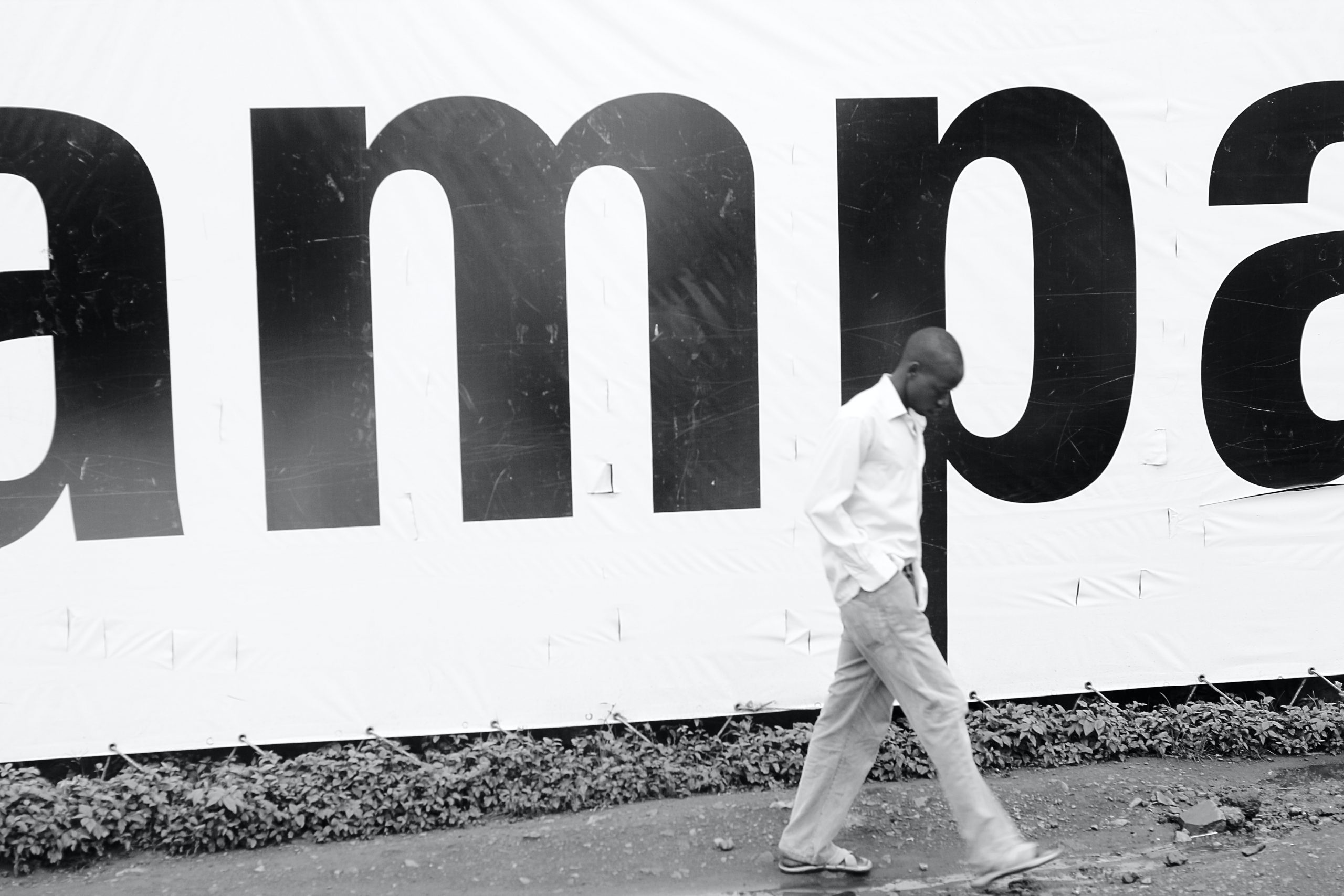 Man walks in front of a Kampala sign