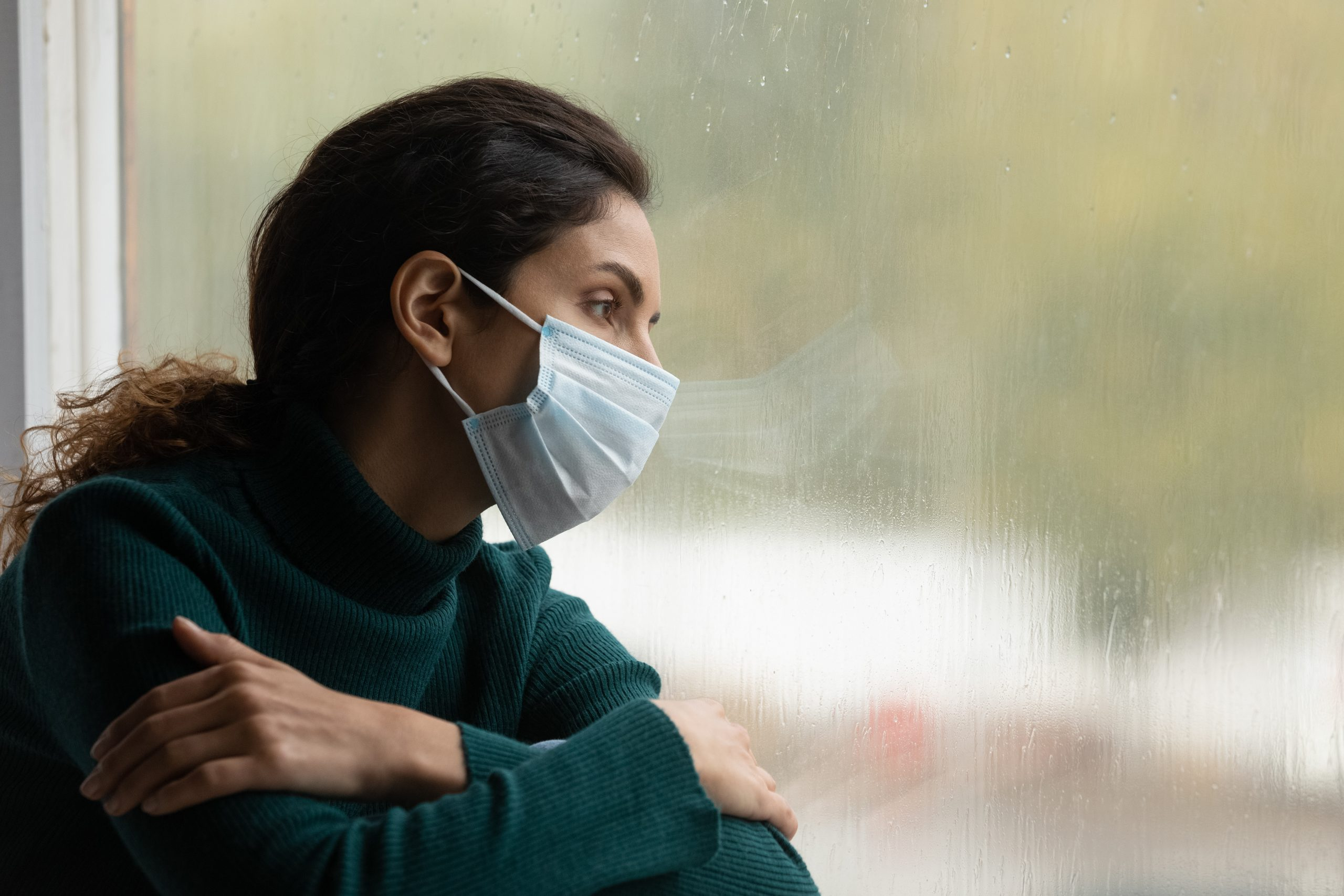 A woman in a face mask looks out through a window. Used to signify looking forward in terms of pandemic preparedness